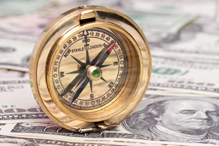 pioneering: many dollar bills and a compass. cloes up