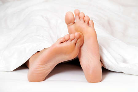 peoplesoft: two feet in bed looking out from under a blanket.