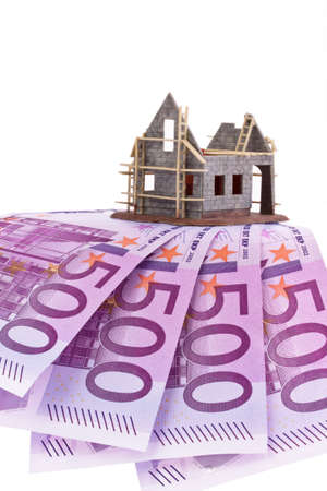 single familiy: many euro banknotes and shell of a house Stock Photo