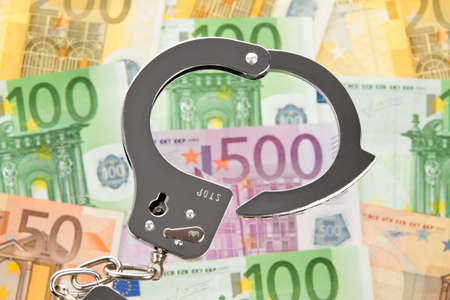 a lot of  euro bank notes with handcuffs Stock Photo - 11854464