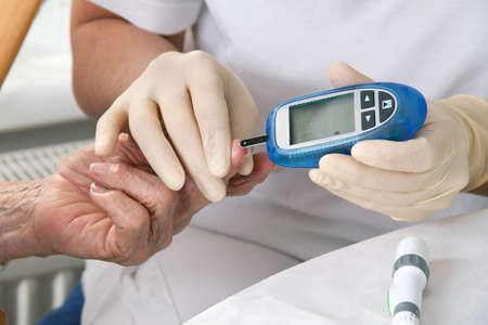 blood glucose meter. the blood sugar value is measured on a finger photo