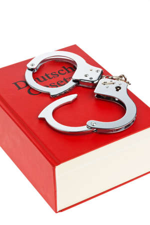 criminal act: a deusch code on a white background with handcuffs. Stock Photo