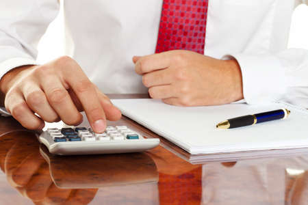 examiner: businessman with a calculator. calculation of costs, revenue, balance sheet Stock Photo