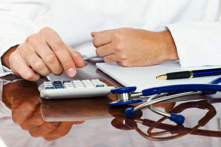 hospital fees: doctor with a calculator. calculation of costs and revenues in physician practice and hospital