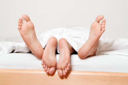 in chief a couple feet in bed. love, sex and partners. Stock Photo