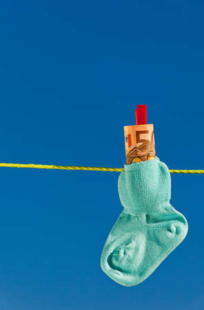 care allowance: baby socks on clothesline with euro banknotes. blue sky.