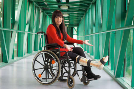 damaged roof: young woman with plaster leg sitting in a wheelchair