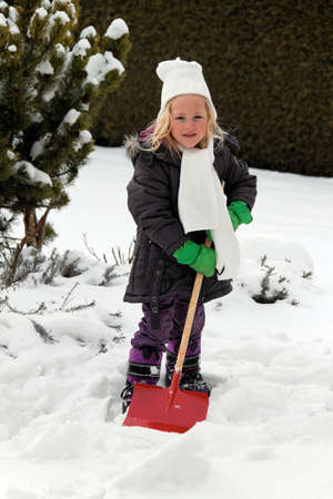 freetime activity: snow shoveling snow shovel in the winter. child has fun on the snow in winter