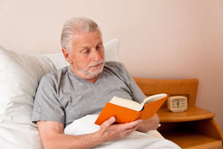 freetime activity: a senior in the nursing home to read the book in bed