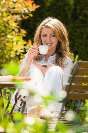 coffee time: young woman drinking coffee at breakfast in the garden
