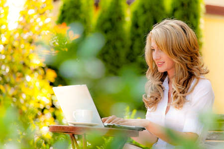 wlan: woman with laptop in the garden. internet outdoors own