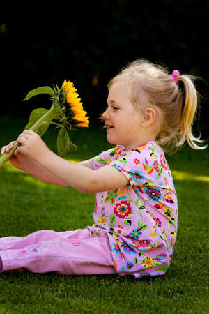 small child with a sun flower in the garden in summer photo