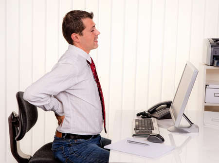 arthritis back: young man in office with computer and back pain