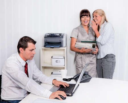illegally: bullying in the workplace an office. two laugh about colleagues Stock Photo