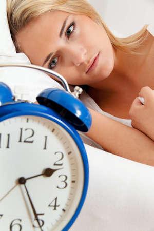 insomnio: reloj con el sueño por la noche. mujer no puede dormir.