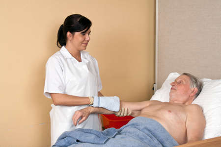 nursing allowance: a nurse washes a patient in a nursing home Stock Photo