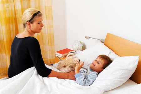 werkende moeder: een moeder en een ziek kind in bed. influenza. kinderziekten.
