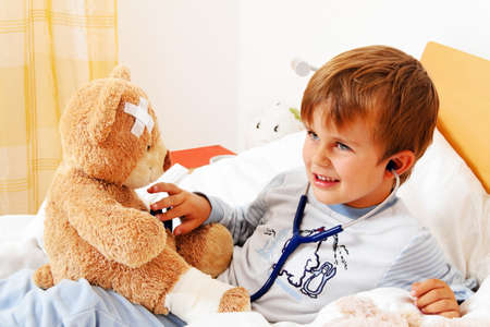 bedridden: a sick child examined teddy with stethoscope