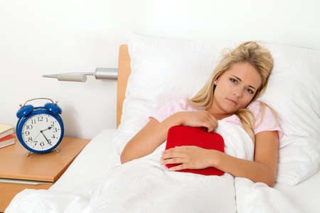 menstrual: a woman with abdominal pain lying in bed and has a hot water bottle
