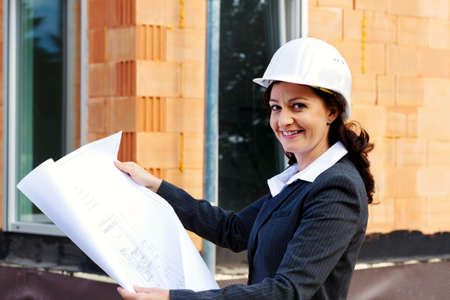freelancers: architect with blueprint before shell of a house building a house. Stock Photo