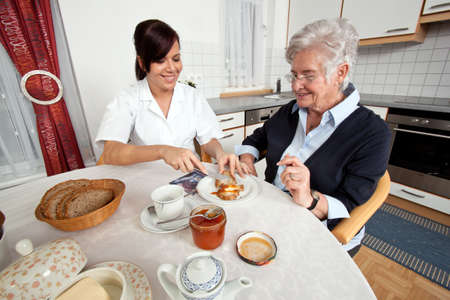 care at home: a geriatric nurse helps elderly woman at breakfast