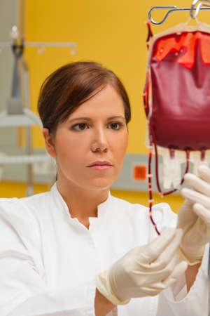 hemorragias: una enfermera en el hospital con los productos sangu�neos. la infusi�n de sangre de un donante. Foto de archivo