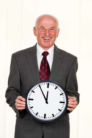 freelancers: a manager keeps a clock. on the dial, it is 11:55 Stock Photo