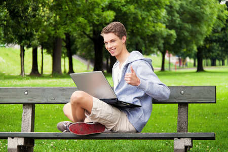 a teenager with laptop outdoors. sitting in the park mobile internet photo