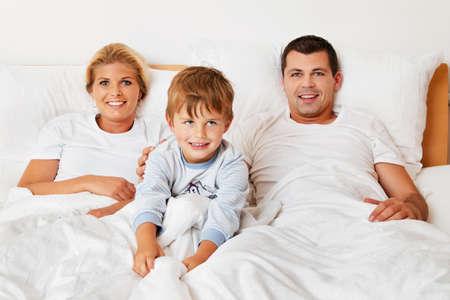 joie: eine junge Familie ist im Bett im Schlafzimmer