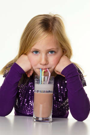 low fat: a small child drinking hot chocolate. against a white background.
