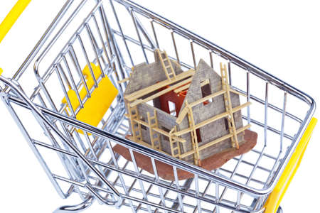 a model of a shell building in a shopping cart. photo icon for house purchase. photo