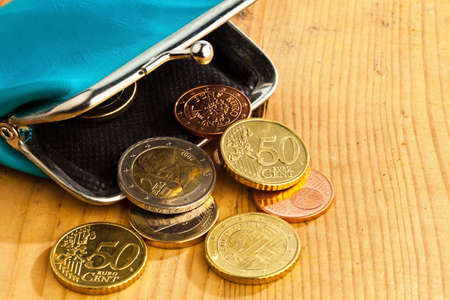 budget crisis: an empty wallet with a few euro coins. photo icon on debt and poverty