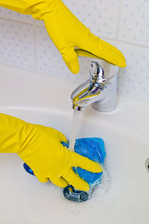 the sink of a bathroom is cleaned with latex gloves  photo