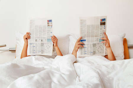 impotence: couple reading a newspaper in bed Stock Photo