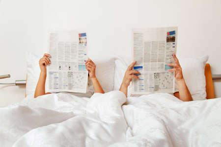 Paar eine Zeitung lesend im Bett