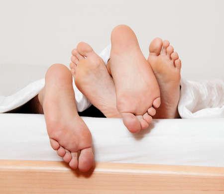 sex: deuken een paar voeten in bed liefde, seks en partners Stockfoto