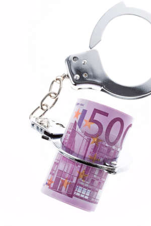 remand: symbol of economic crime  handcuffs and €