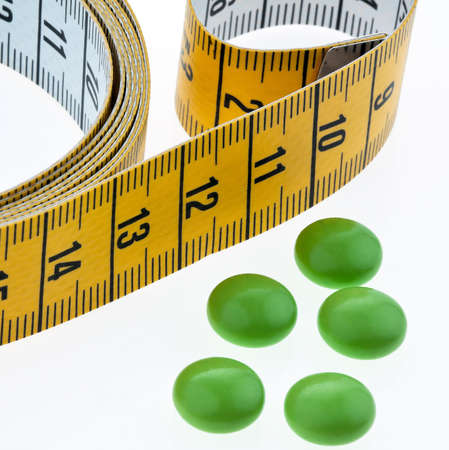 tape measure and tablets, as a symbol for diet pills  remove Stock Photo - 13143368