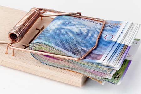 swiss franc: many swiss francs banknotes in mouse trap Stock Photo