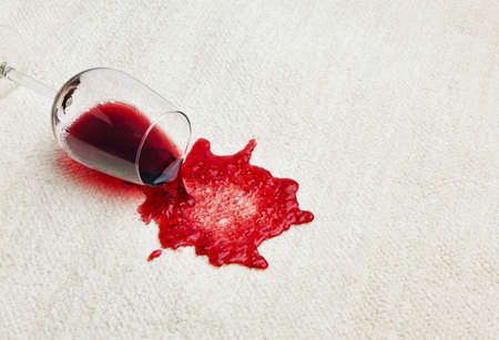 reverse: red wine is spilled on a carpet  reverse glass and all related Stock Photo
