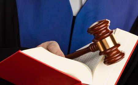 giurisprudenza: un giudice con un libro di legge in tribunale martelletto in mano