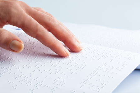 barrier free: fingers and braille  blind people read a book in braille