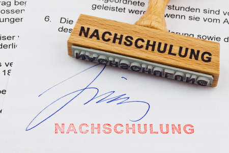 retraining: a stamp made of wood lying on a document  german inscription  retraining