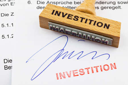 a stamp made of wood lying on a document  german inscription  investment photo