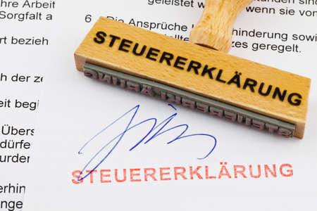 retour: een stempel van hout liggend op een document Duitse woorden belastingaangifte Stockfoto