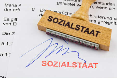 collective bargaining: a stamp made of wood lying on a document  german words  welfare Stock Photo