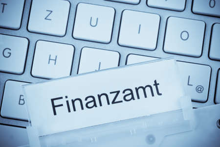 ein Ordner für Dateien in Hängemappen vor einem Computer-Tastatur zum Thema Finanzamt