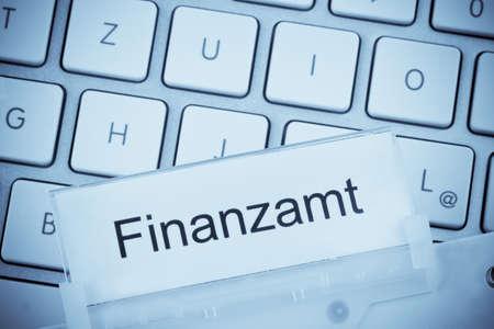 un dossier pour les fichiers en dossiers suspendus devant un clavier d'ordinateur sur le bureau des impôts sujet