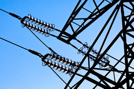 the poles of a power line against a blue sky  high voltage power line photo