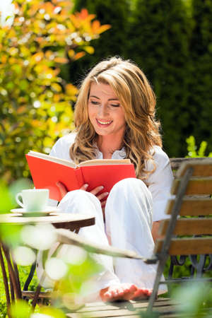 inform information: woman reading a book in the garden Stock Photo